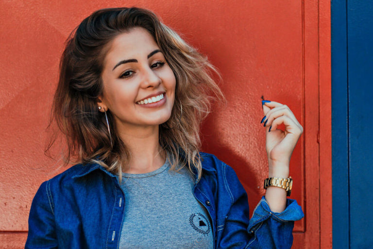 A smiling young woman showing off her dental veneers
