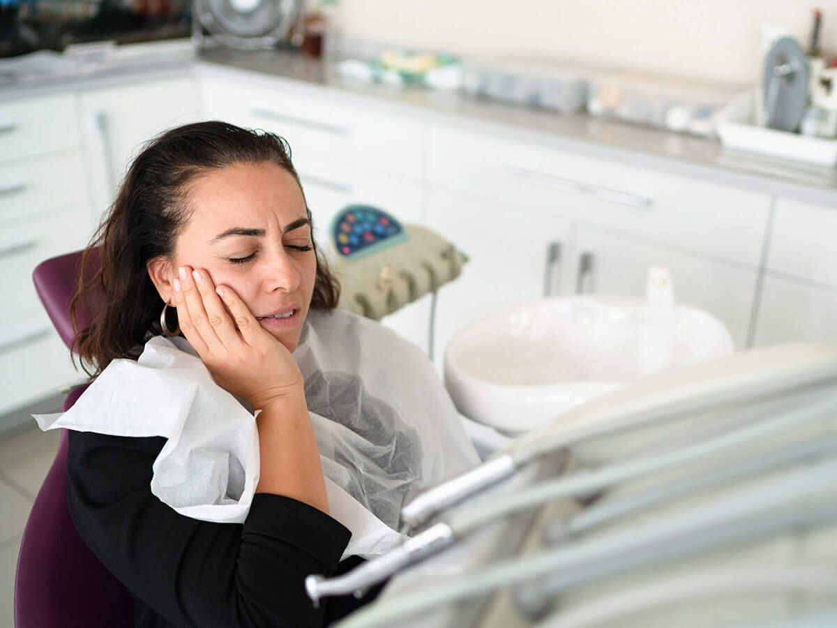 A female dental patient holds her mouth in pain while suffering from a dental emergency