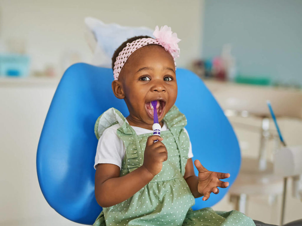 A young girl sits in a dental exam chair with a toothbrush in her mouth at a pediatric dentistry appointment