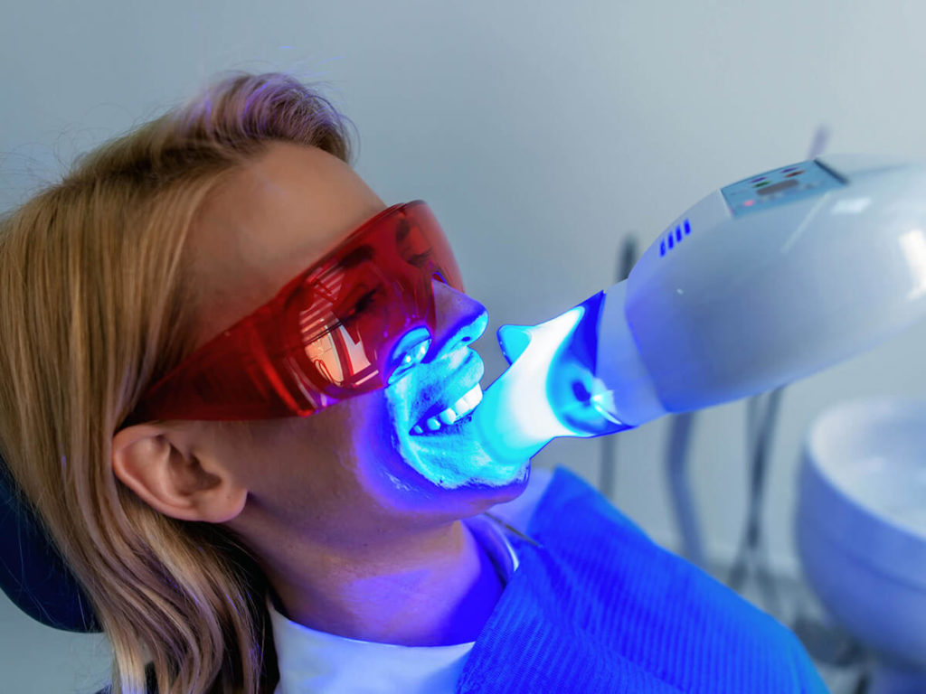 A dental patient receiving in-office teeth whitening using a laser
